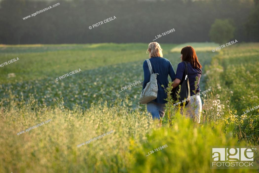 Stock Photo: Two young woman walking together.