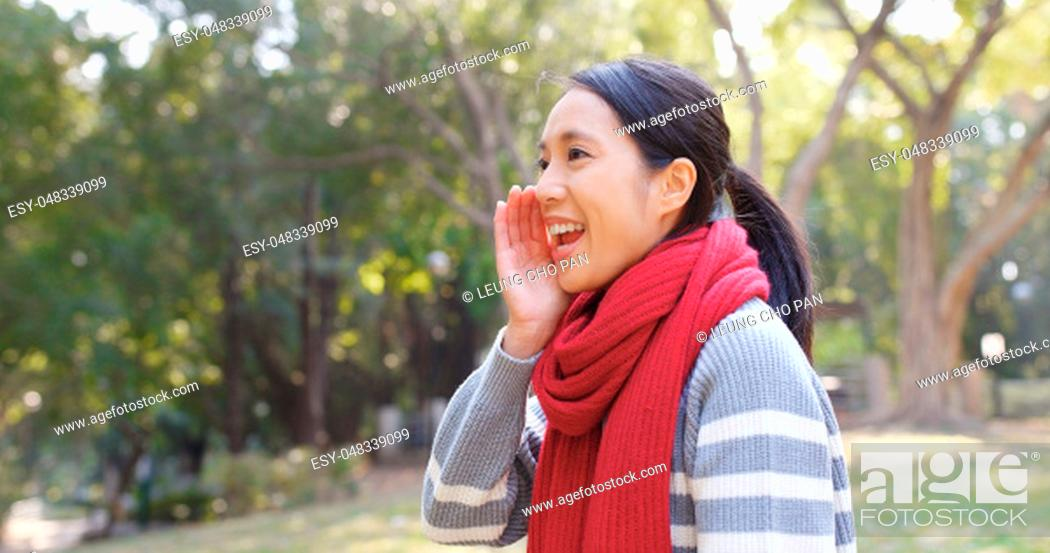 Stock Photo: Happy woman standing at park and yelling for something.