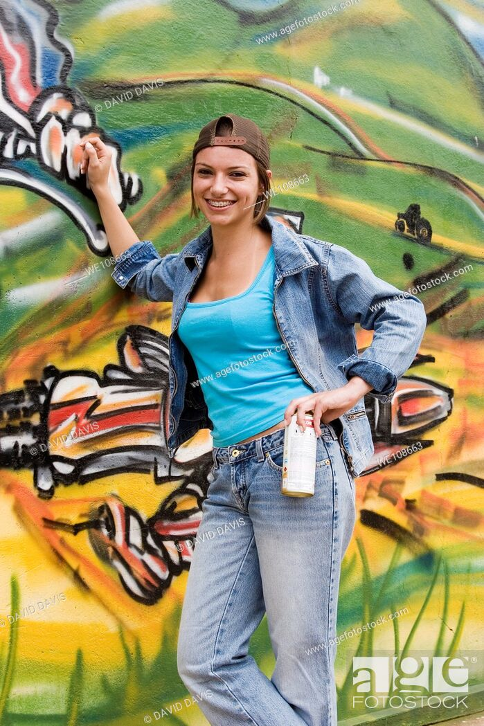 Stock Photo: Beautiful Brazilian girl spray painting a mural on the side of a building.