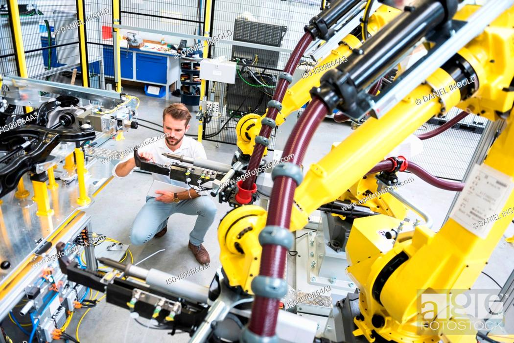 Stock Photo: Young male engineer testing machinery in engineering factory.
