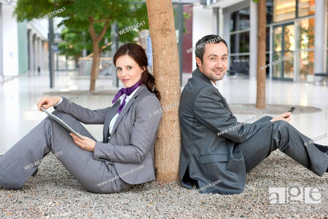 Stock Photo: Germany, Leipzig, Business people sitting at tree with digital tablet and cell phone.