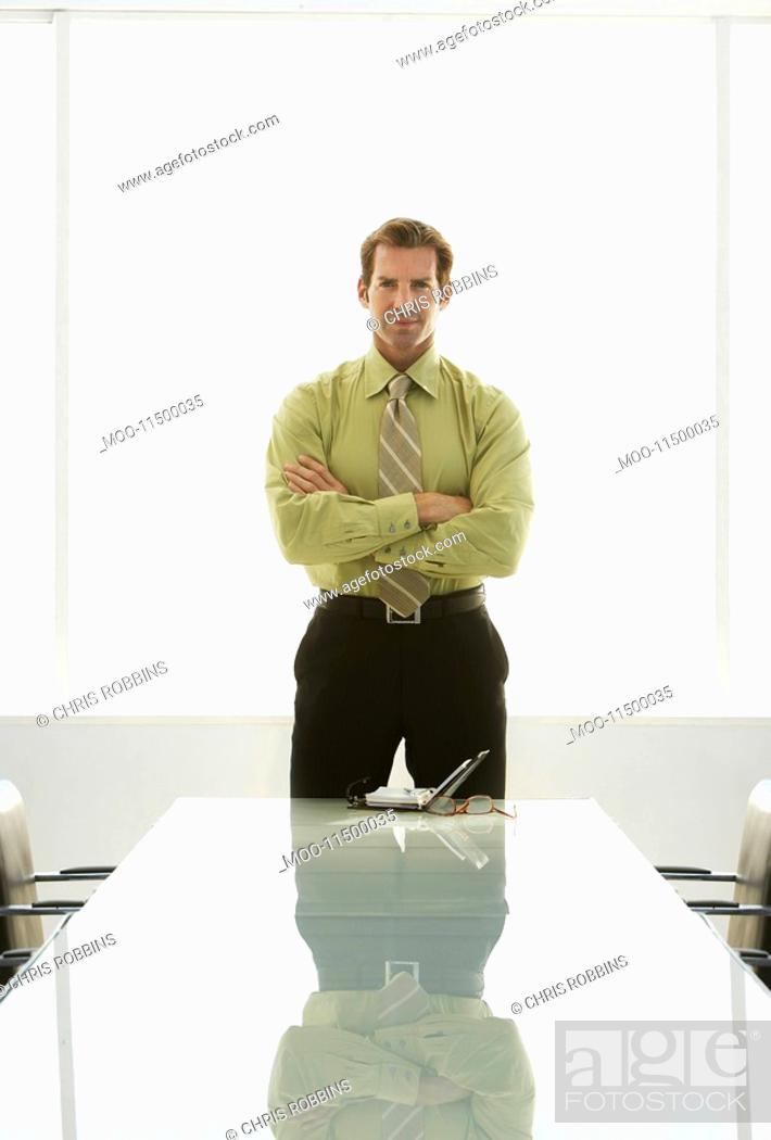 Stock Photo: Businessman with arms crossed at conference table portrait.