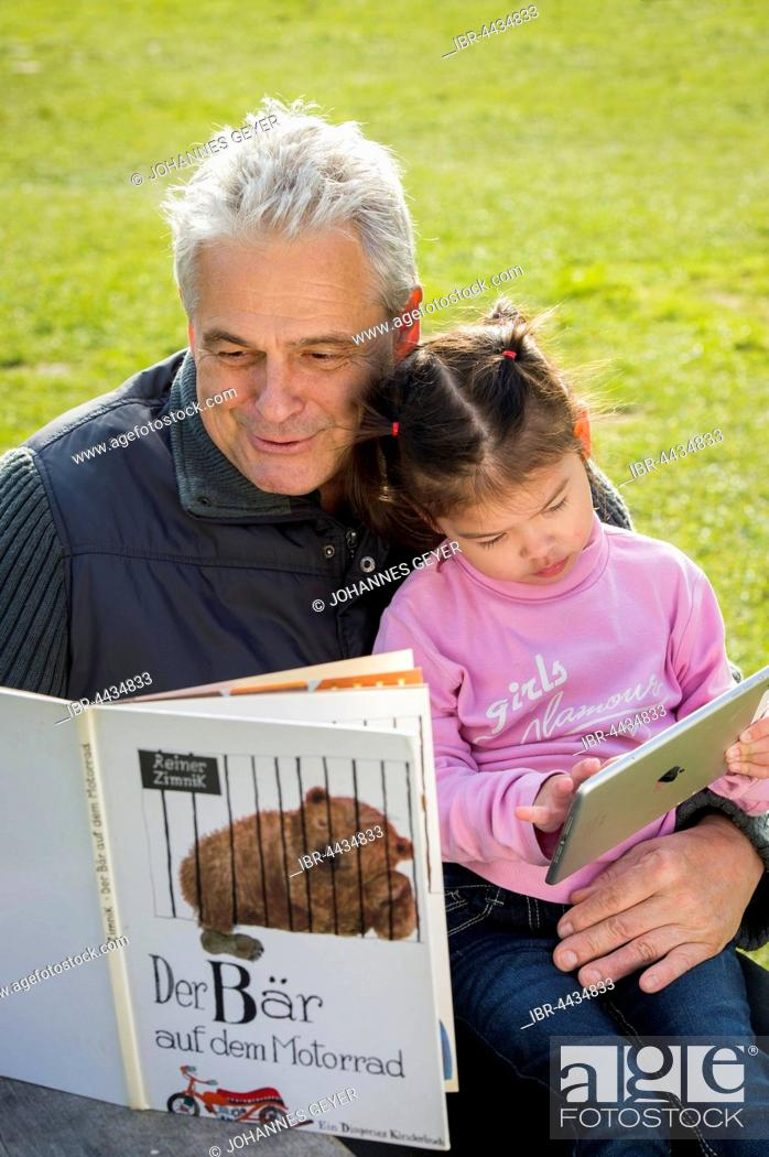 Imagen: Father reading book to daughter, sitting on meadow, girl playing with tablet, Poing, Bavaria, Germany.