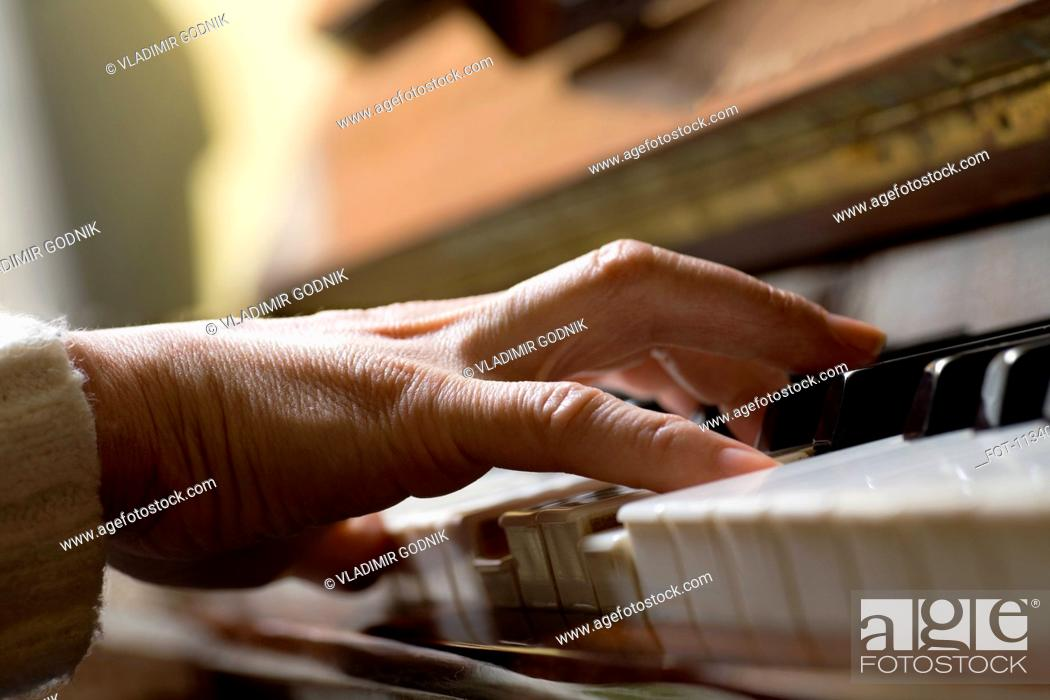 Stock Photo: Piano chord pressed by woman's hand.