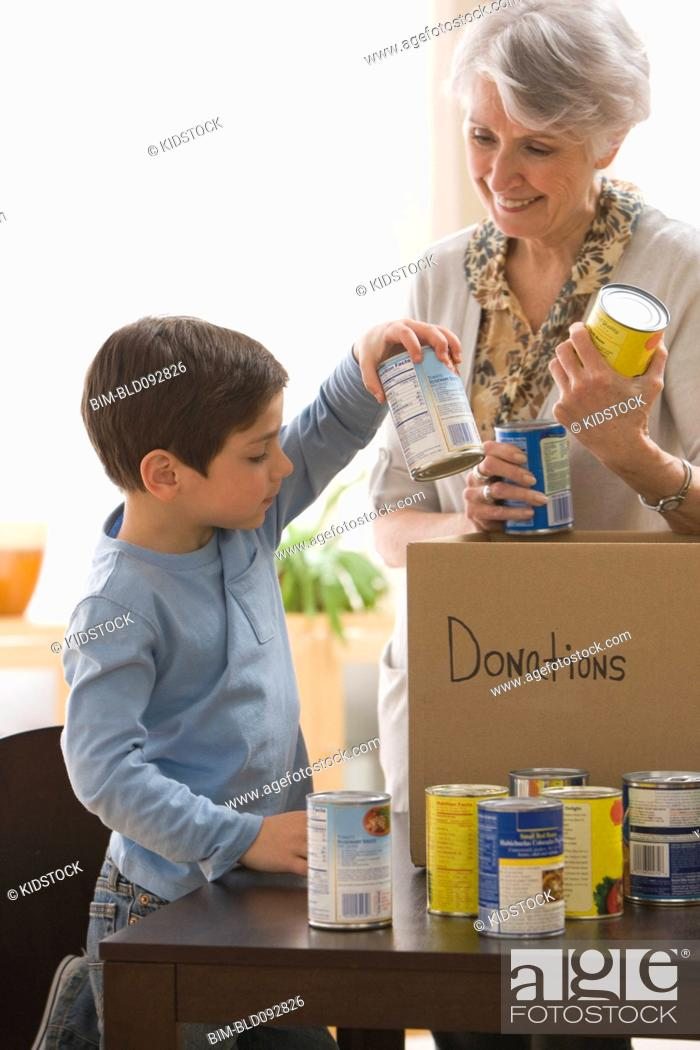 Stock Photo: Caucasian grandmother and grandson filling box with canned goods for charity.