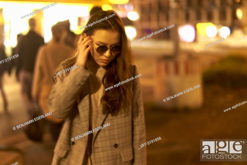 Stock Photo: Fashionable woman on the street by night. Munich, Bavaria, Germany.