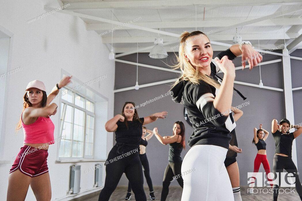 Imagen: Smiling woman practicing dance with friends in studio.