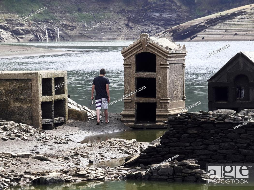 Stock Photo: A young fisherman near an old cemetery flooded by the Belesar reservoir, an artificial swamp that covered the village of Portomarin in 1963 on the Miño river.