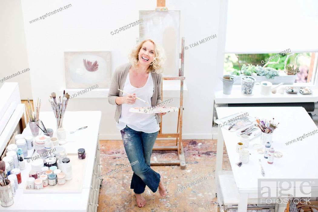 Stock Photo: Woman holding paintbrush and palette in art studio.