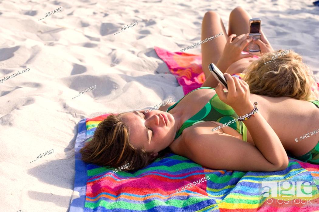 Stock Photo: Teenage girls with mobile phones sunbathing on beach, one with head on friend.