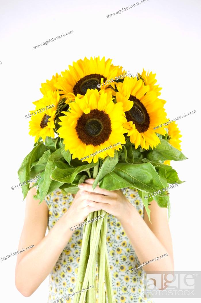 Stock Photo: A Young Woman Behind A Bunch Of Sunflowers.