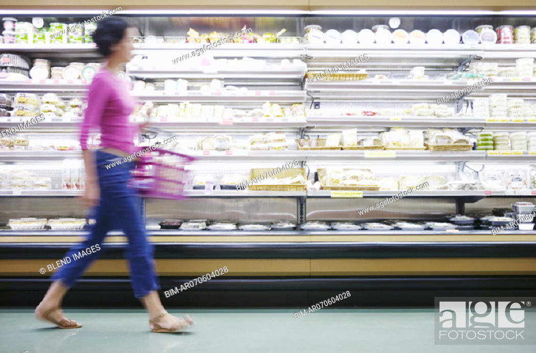 Stock Photo: Blurry woman walking in grocery store.