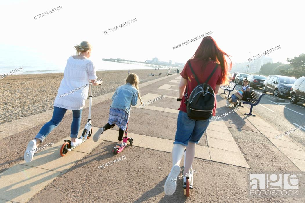 Stock Photo: Lesbian couple with daughter riding push scoters on sunny beach boardwalk.