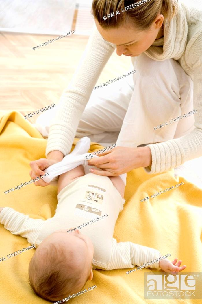 Stock Photo: mother dressing up baby.