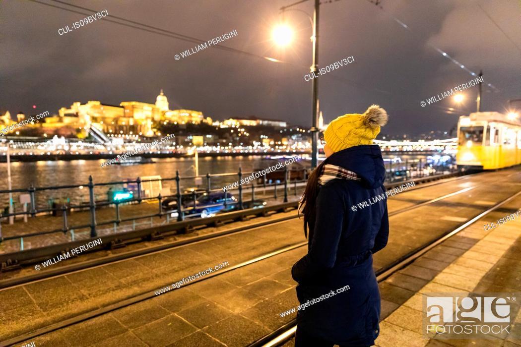 Stock Photo: Woman enjoying scenery by river at night, Budapest, Hungary.