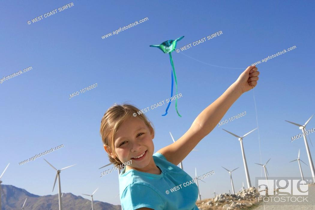 Stock Photo: Girl 7-9 with kite on wind farm portrait.