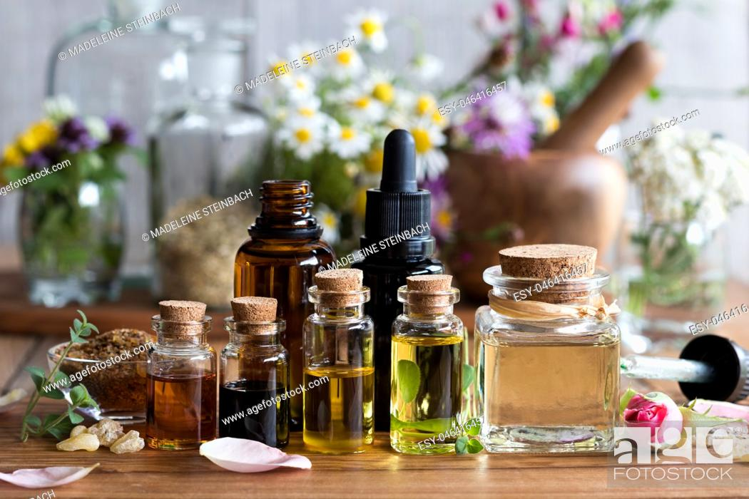 Stock Photo: Selection of essential oils with various herbs and flowers in the background.
