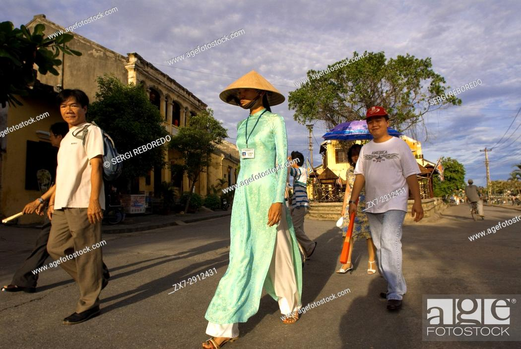 Stock Photo: A guide along with several tourists through the old city of Hoi An, Vietnam.