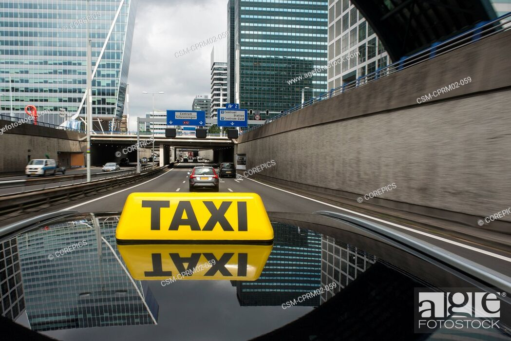 Stock Photo: City taxi driving over a motorway in a commercial district.