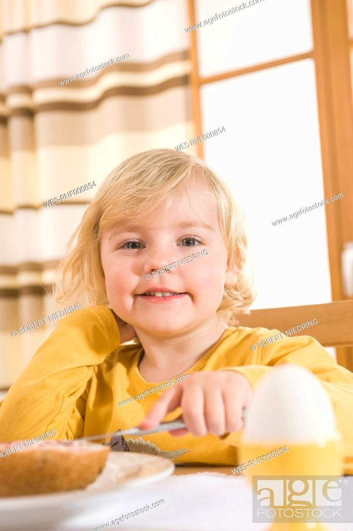 Stock Photo: Girl spreading jam on bread, smiling, portrait.