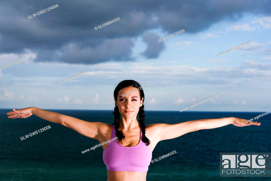 Stock Photo: Portrait of a young woman with her arms outstretched.