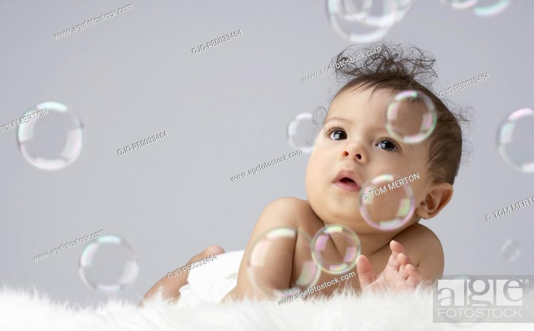 Stock Photo: A baby surrounded by bubbles.