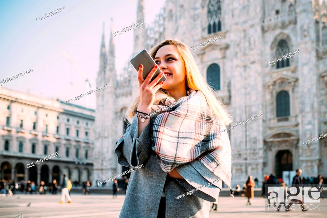 Stock Photo: Young female tourist talking at smartphone by Milan Cathedral, Milan, Italy.