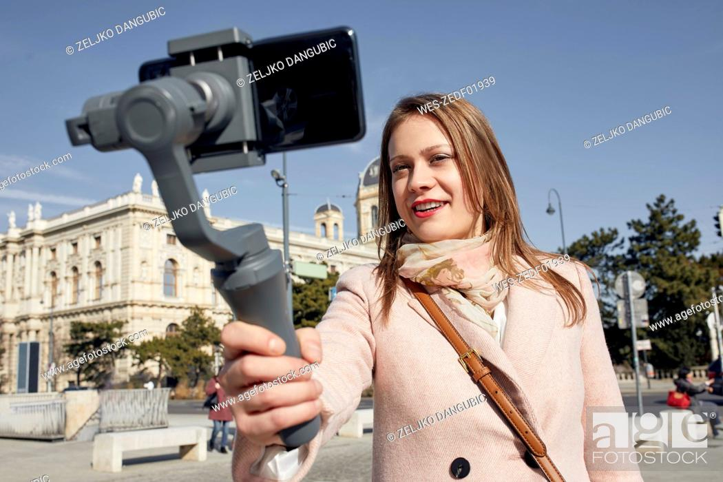Stock Photo: Austria, Vienna, portrait of smiling young woman using selfie-stick for taking photo with smartphone.