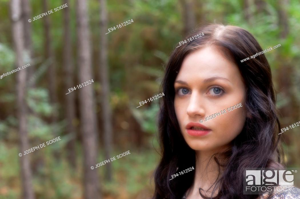 Stock Photo: Portrait of a 20 year old brunettte woman looking directly at the camera outdoors.