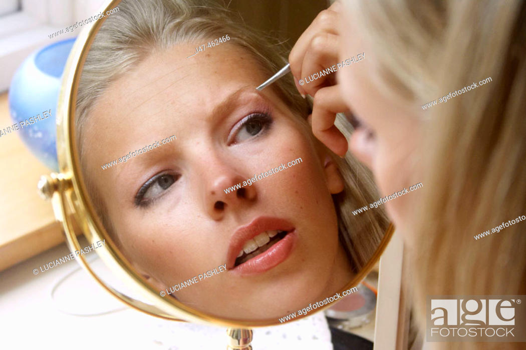 21 Year Old Girl Looking In The Mirror Plucking Her Eyebrows Stock