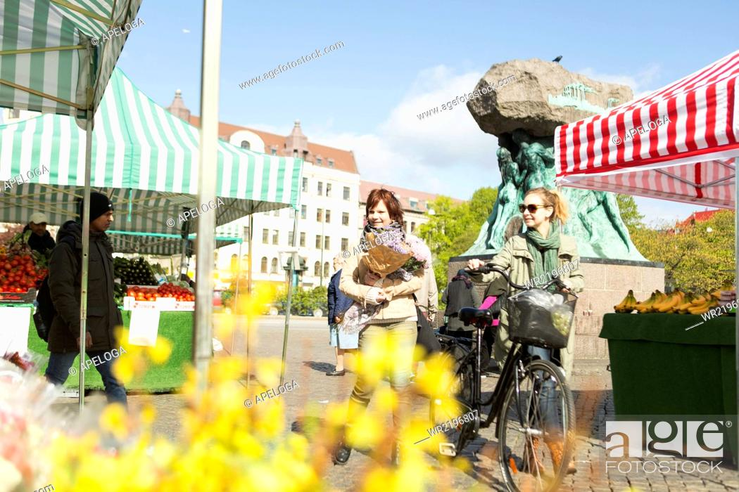 Stock Photo: Mature women with bicycle walking in market.