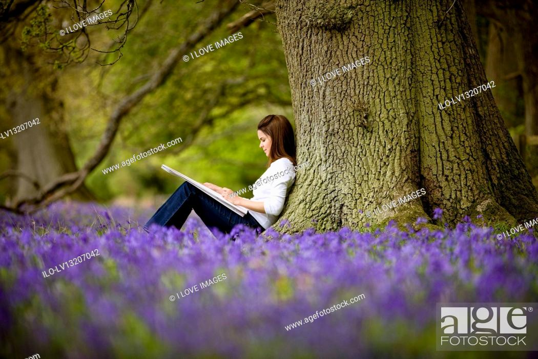 Stock Photo: A young woman leaning against a tree, drawing.