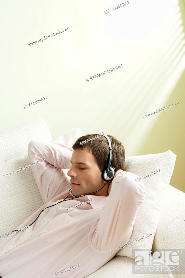 Stock Photo: Young man listening to music on the couch.