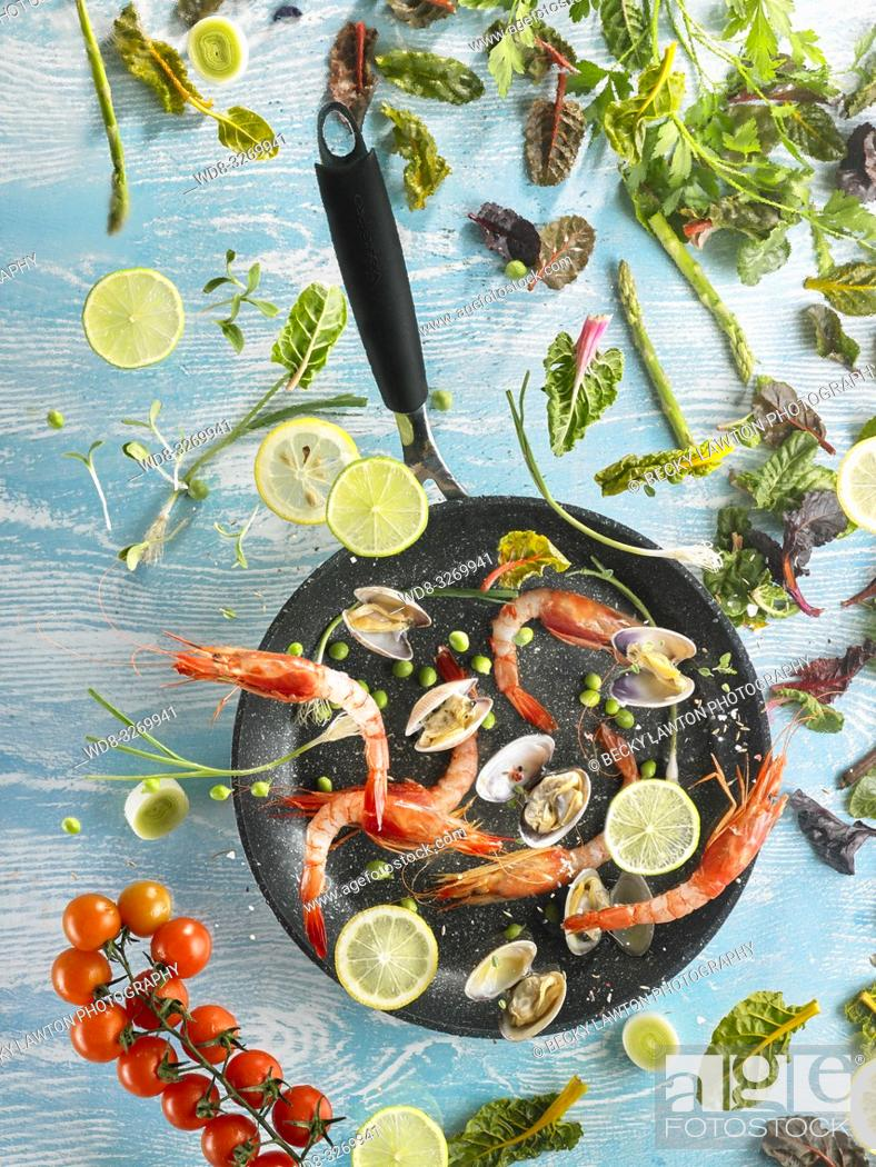 Stock Photo: Composition with vegetables and seafood, flying over a frying pan, with blue background.