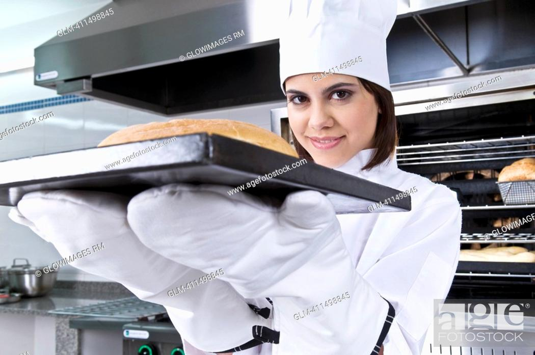 Stock Photo: Female chef holding a bun in a tray.