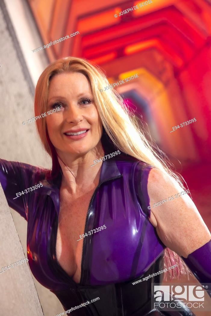 Stock Photo: A beautiful 51 year old tall blond woman dressed a latex costume in a lighted underpass.