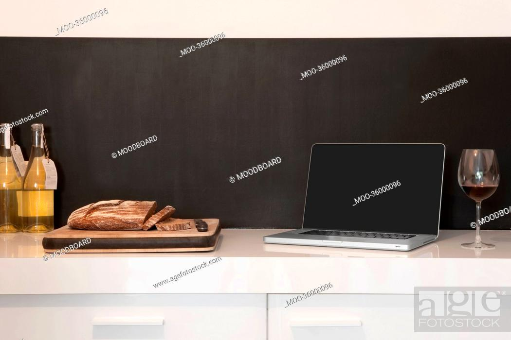 Stock Photo: Laptop, wineglass and bread loaf on counter.