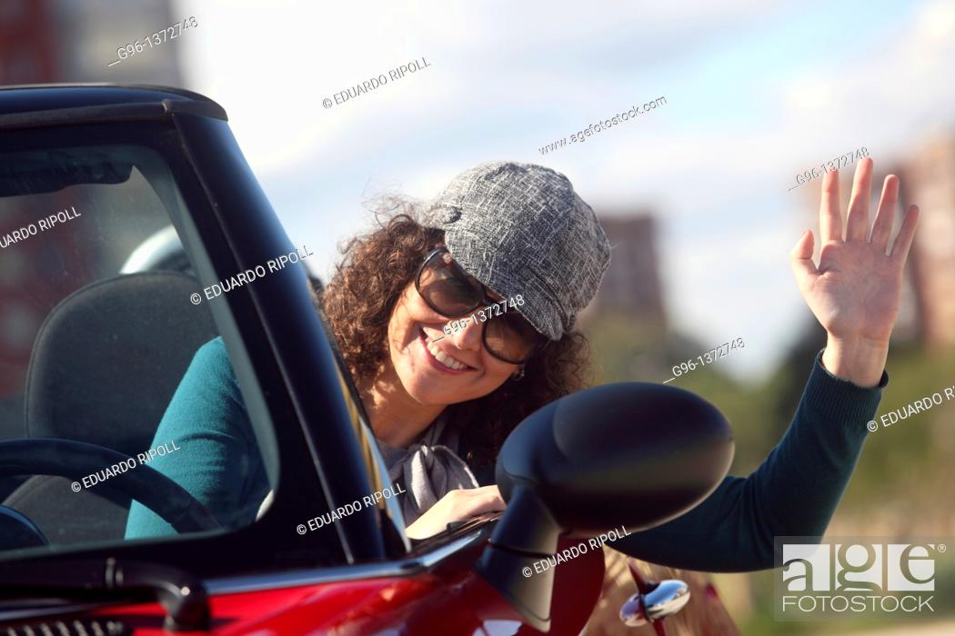 Stock Photo: woman in a convertible relaxing at the beach.