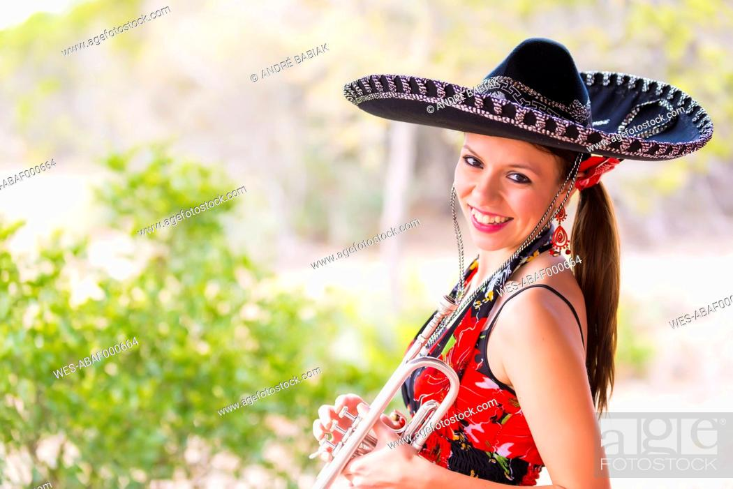 Stock Photo: USA, Texas, Young woman holding trumpet, smiling, portrait.