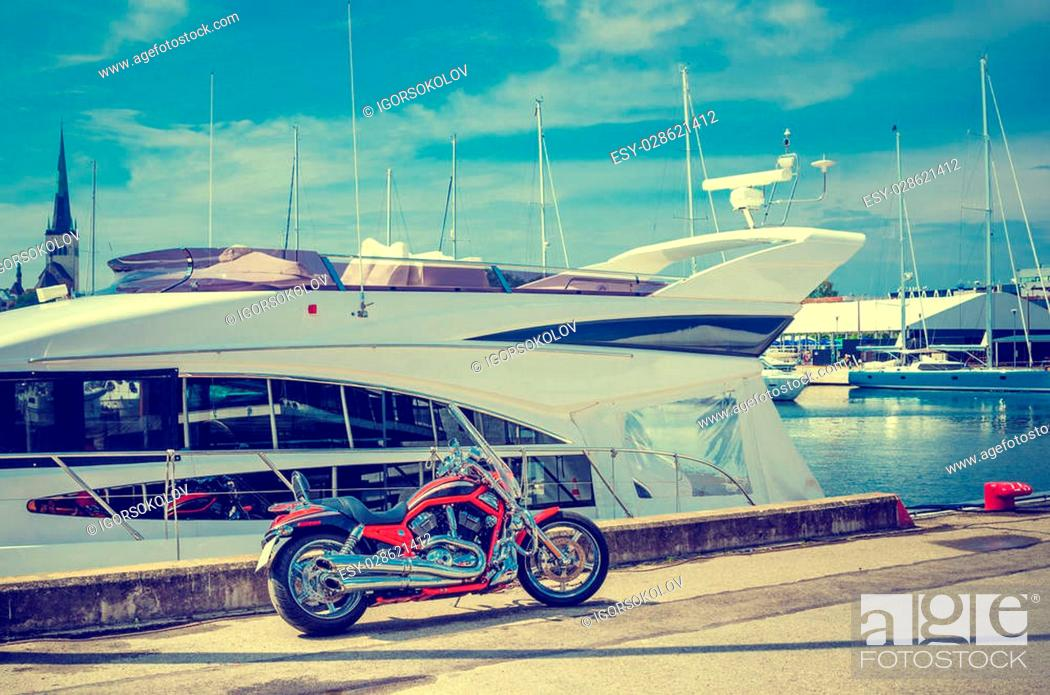 Stock Photo: Beautiful motorcycle on the pier on the background of yachts. Cross process.