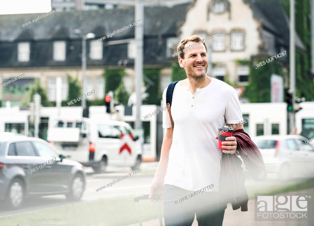 Stock Photo: Smiling man with rolling suitcase and takeaway coffee walking in the city.
