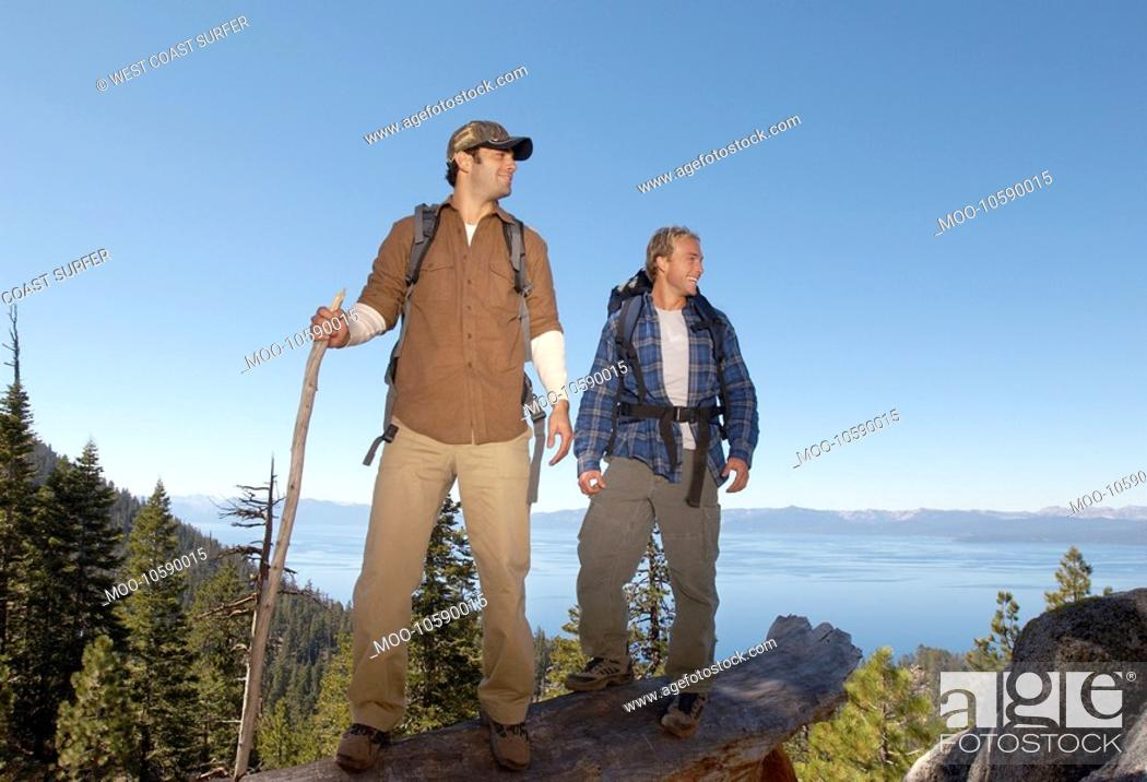 Stock Photo: Two male hikers on log near forest.