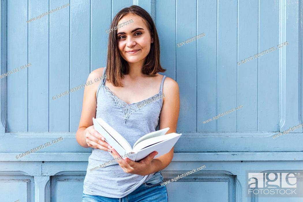 Stock Photo: Young girl smiles and holds a bluish gray open white paper.