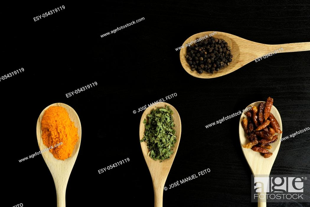 Stock Photo: four wooden spoons with saffron, oregano, chillies and black pepper on dark background from above.