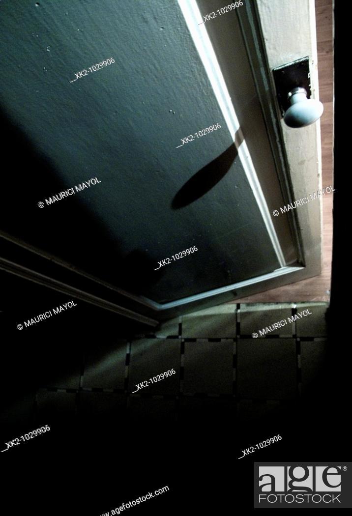 Stock Photo: misteriosa puerta abriendose y proyectando sombras en el suelo i el pomo.