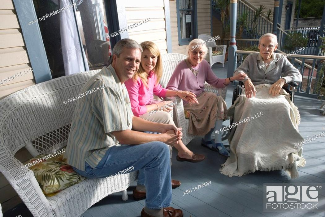 Imagen: Family with elderly parents and adult children sitting together on front porch.
