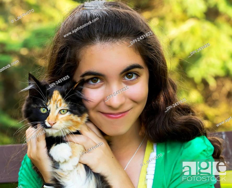 Stock Photo: Portrait of a young girl holding a cat outdoors; Sherwood Park, Alberta, Canada.