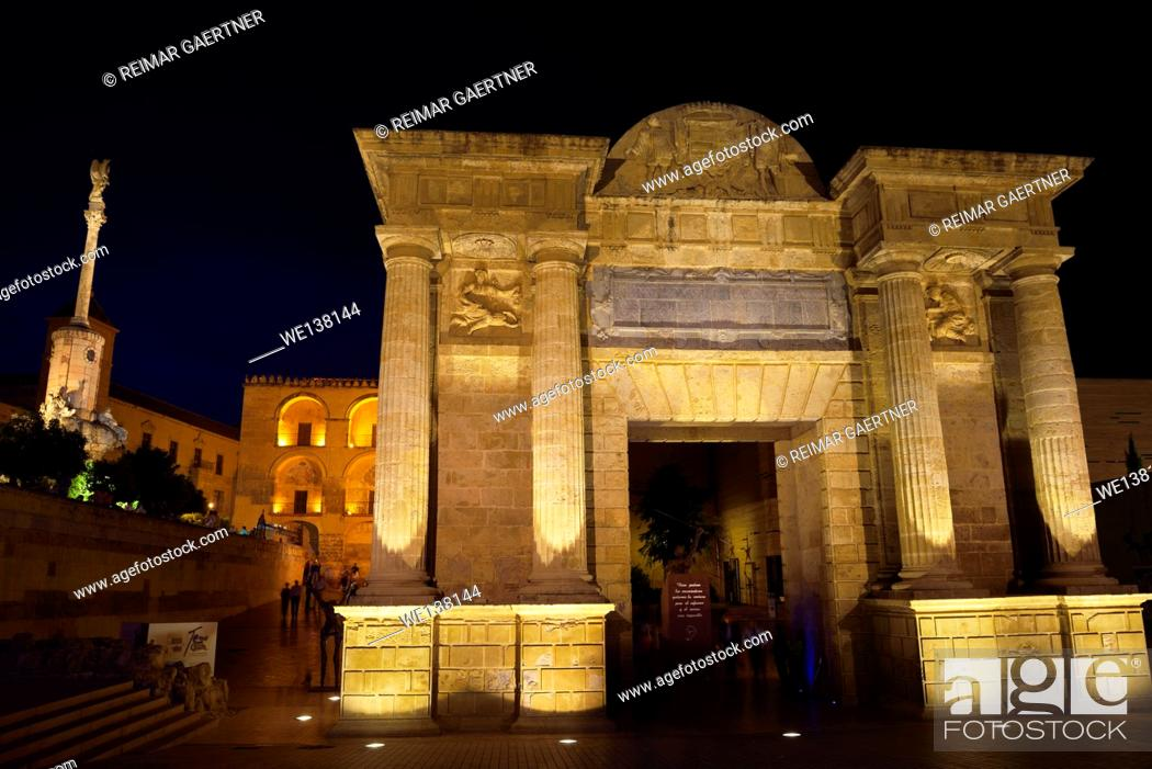 Stock Photo: Puerta del Puente Roman Bridge Gate at night with Saint Raphael triumphal statue and Cordoba Cathedral.