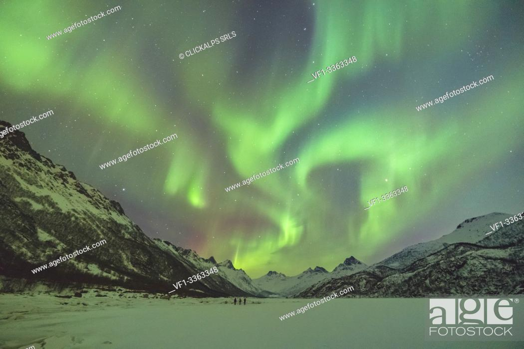Stock Photo: Northern lights with mountains and three people in winter. Kleppstad, Nordland county, Northern Norway, Norway.