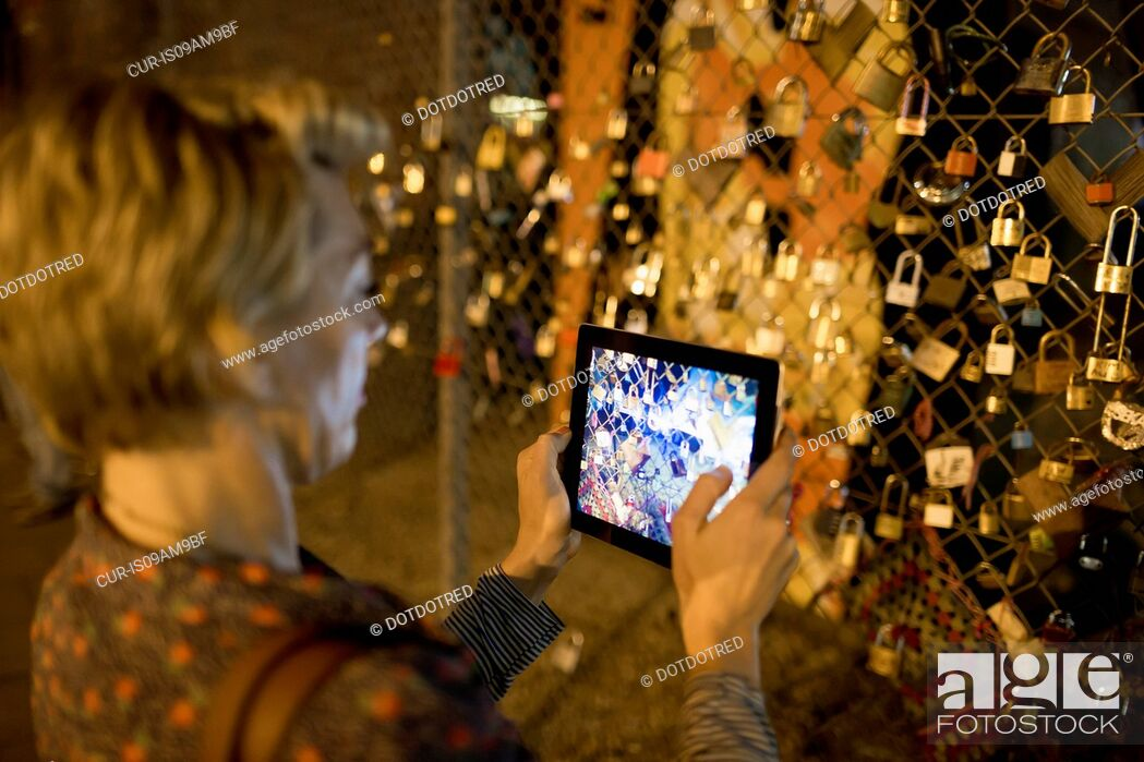 Imagen: Mature woman photographing love locks on fence at night, London, UK.